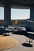 Outdoor furnishings; sisal rug, bean bag and chairs on sunny ramp of concrete building