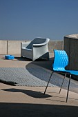 Modern outdoor furnishings - chair with blue shell seat, woven rug and plastic armchair in background