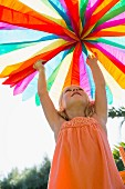 Little girl playing with colourful paper decoration in garden
