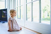 Little girl sitting on floor looking through French windows