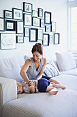 Mother tickling young daughter on sofa