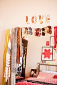 Scarves, belts and sunglasses hanging on mirror reflecting a bed with red bed linen and ornaments