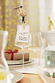 A tightrope walker figure on a clothes peg holding a menu to a wine glass