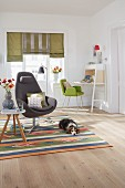 A grey armchair with a neck rest and a simple side table on a patterned rug with a dog in a living room