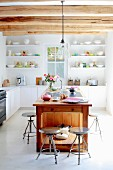 Vintage metal stools around free-standing, solid-wood kitchen island under wood-beamed ceiling with modern fitted shelves and cupboards in background
