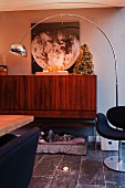 Retro arc lamp in front of small Christmas tree on top of wooden sideboard with metal frame