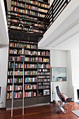 Two-storey bookcase and white bicycle on integrated gallery above Eames chair