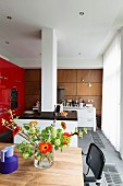 View from dining area into designer kitchen with island counter encircling white, masonry pillar and fitted cupboards with red fronts