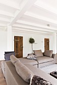 Elegant, pale grey sofa combination in open-plan interior with rustic charm and white, wood-beamed ceiling