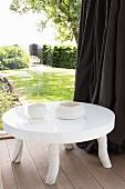 Weisser Bodentisch mit hochglänzender Platte und rustikalen Füssen vor Glasfront, Blick in sommerlichen Garten