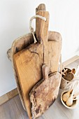 Old wooden chopping boards and kitchen utensils in wooden containers on floor