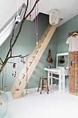 Feminine attic room with wooden ladder and white dressing table against pastel green wall