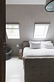 Bed with button-tufted frame below skylights in sloping ceiling