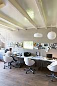 Mann an Schreibtisch mit weissen Drehstühlen in modernem Büro mit weisser Holzbalkendecke