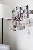 Standard lamp with white lampshade in front of photos from magazines on white wall