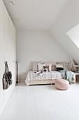 Rosa Sitzpouf auf weissen Dielenboden vor romantisch gestaltetem Bett mit Kissen und Tagesdecke