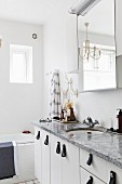Stone washstand counter with white base cabinets and leather handles below mirrored cabinet and chandelier in white bathroom