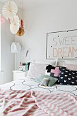 Patterned scatter cushions and striped blanket on double bed in romantic bedroom