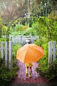 Kleines Mädchen mit orangefarbenem Regenschirm unter einem Rosenbogen im Garten