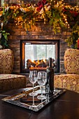 Wine glasses and wine bottle in living room at Christmas
