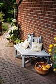 DIY wooden bench painted pale grey and white against brick wall