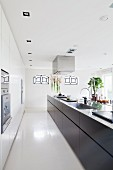 Long, free-standing kitchen counter with black base units in designer kitchen with recessed spotlights in suspended ceiling