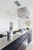 Long, free-standing kitchen counter with dark base units in designer kitchen