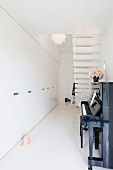 Narrow foyer with white fitted cupboards, upright piano and staircase with white treads
