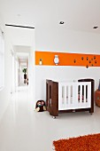 Cot below orange stripe on wall in nursery; open doorway with view into corridor