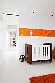 Cot below orange stripe on wall in nursery; open doorway with view into corridor