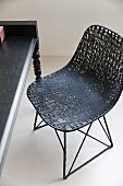 Shell chair with black mesh seat on metal frame next to table