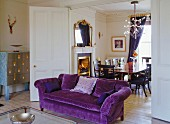 Georgian Chesterfield sofa with purple upholstery, Italian, designer cabinet with silver front and folding, sliding doors leading to elegant dining room