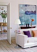 Sofa, standard lamp and console table below modern artwork; view of antique console table in hallway through open door
