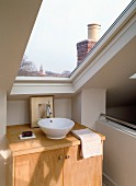 Modern washstand with base cabinet and countertop sink under skylight with a view