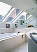 Bathtub with marble surround below row of skylights; mirrored wall with niche in background