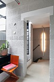 Zig-zag chair against breeze block wall in hallway; vertical strip light on wall in background
