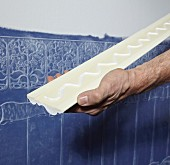 Attaching stucco moulding to edge Lincrusta wallpaper (structured linoleum wallpaper) on wall