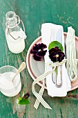 White linen napkin with cutlery and pansies
