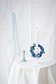 Small forget-me-not wreath draped over white candle in candlestick