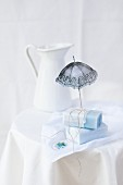 Forget-me-not soap and cut out paper parasol on cloth with forget-me-not motif