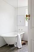 Free-standing, vintage-style bathtub on concrete floor in white bathroom