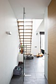 View from hallway into dining area with staircase and ride-on cars on grey tiled floor