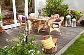 Comfortable seating area with wicker furniture on DIY wooden terrace with basket of cushions in foreground