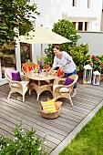 Gemütlicher Sitzplatz mit Rattanmöbeln unter Sonnenschirm und Frau auf selbstgebauter Holzterrasse