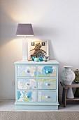 Alte Kommode im neuen Look durch pastellblauen Anstrich und mit Tapete beklebte Schubladenfronten