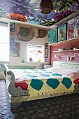 Colourful bedroom in mixture of patterns: ornate rug, floral wallpaper on ceiling and patterned quilt on bed