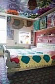 Buntes Schlafzimmer in Mustermix: Ornamentteppich, Blumentapete an der Decke und Quilt auf dem Bett