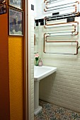 Artistic arrangement of heating pipes above vintage-style sink on tiled wall