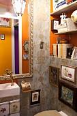 Opulent dekoriertes Gäste-WC mit Ornament-Tapete, barockem Spiegel und Bildergalerie