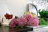 Pink chrysanthemums next to dish of fresh strawberries